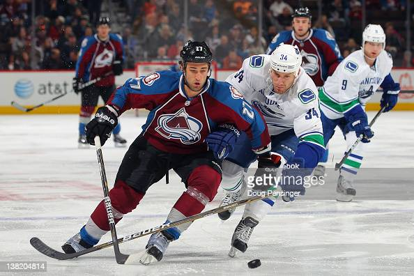 Kyle Quincey of the Colorado Avalanche controls the puck as Byron Bitz of the Vancouver Canucks pursues at the Pepsi Center on February 4 2012 in...