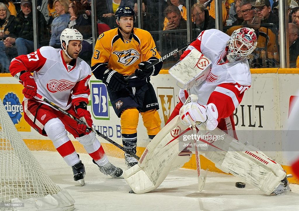 Kyle Quincey #27 of the Detroit Red Wings and Colin Wilson #33 of the Nashville Predators watche goalie Jonas Gustavsson #50 dump the puck at Bridgestone Arena on February 19, 2013 in Nashville, Tennessee.