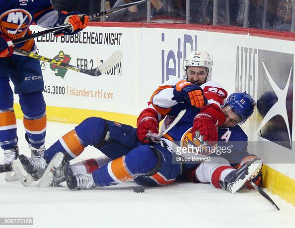 Kyle Quincey of the Detroit Red Wings and Frans Nielsen of the New York Islanders battle for the puck during the second period at the Barclays Center...