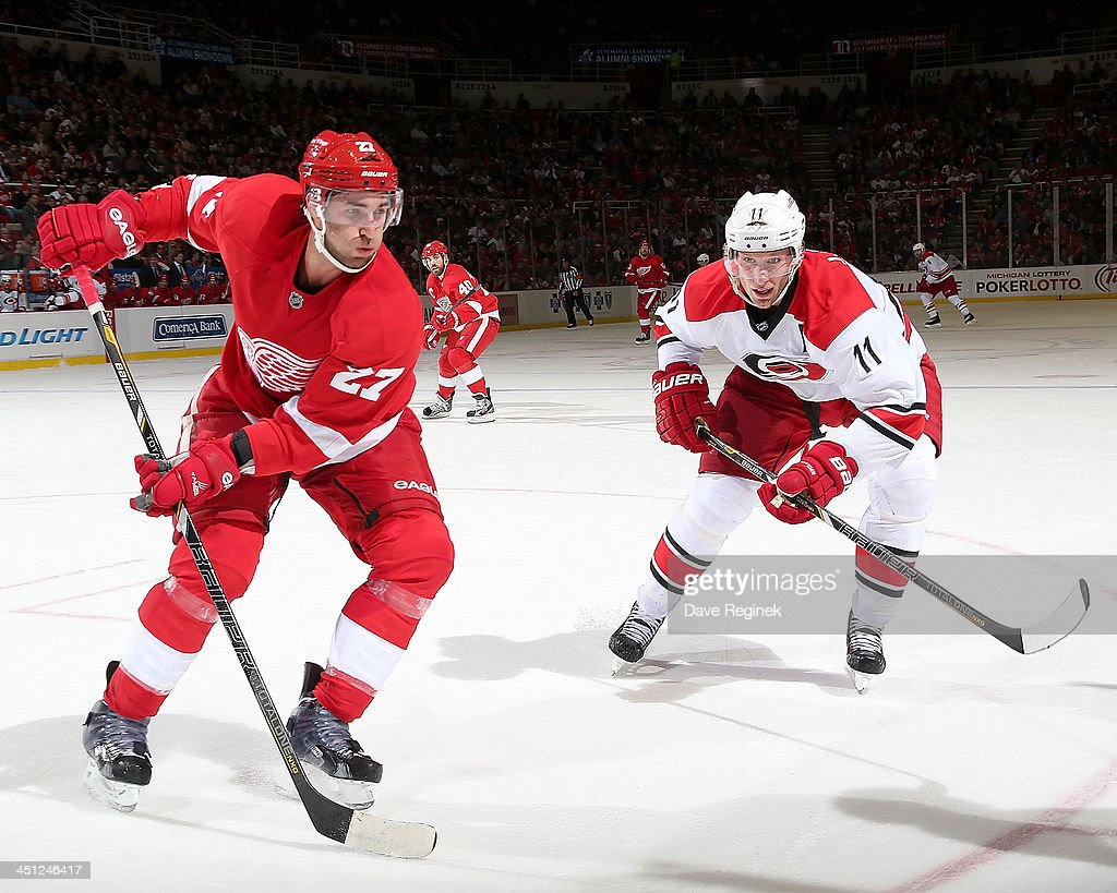 <a gi-track='captionPersonalityLinkClicked' href=/galleries/search?phrase=Kyle+Quincey&family=editorial&specificpeople=2234340 ng-click='$event.stopPropagation()'>Kyle Quincey</a> #27 of the Detroit Red Wings and <a gi-track='captionPersonalityLinkClicked' href=/galleries/search?phrase=Jordan+Staal&family=editorial&specificpeople=533044 ng-click='$event.stopPropagation()'>Jordan Staal</a> #11 of the Carolina Hurricanes race for the puck in the corner during an NHL game at Joe Louis Arena on November 21, 2013 in Detroit, Michigan.