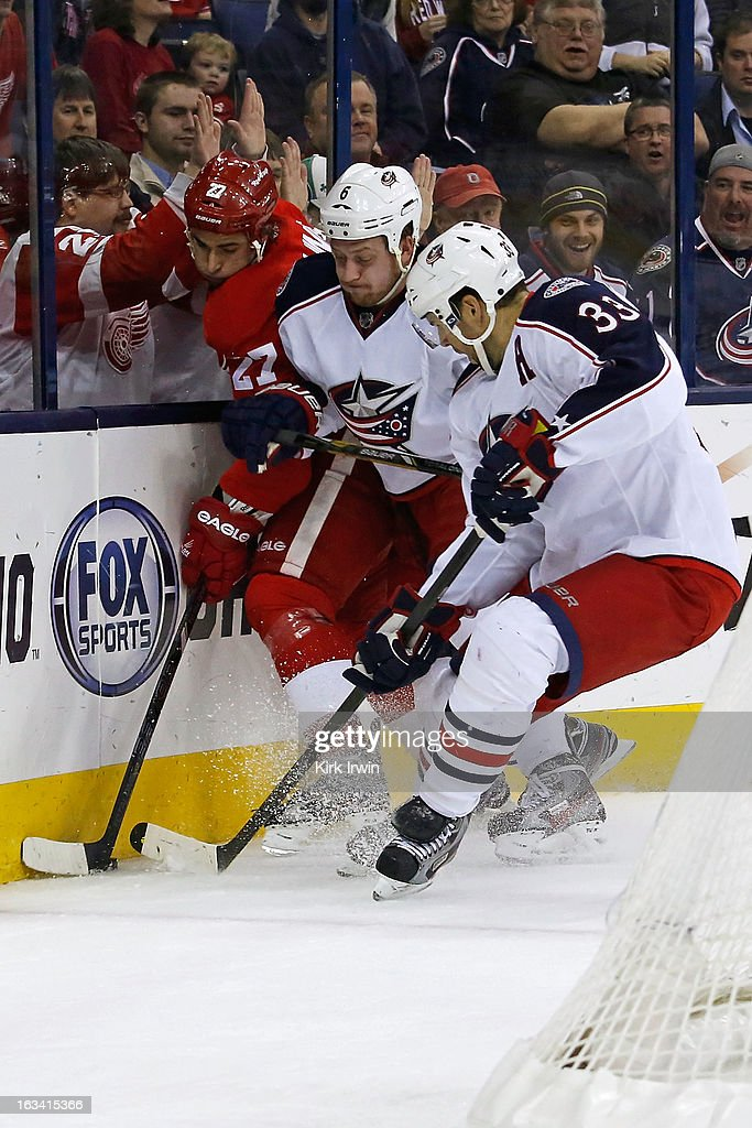 Kyle Quincey #27 of the Detroit Red Wings battles for control of the puck with Nikita Nikitin #6 and Adrian Aucoin #33 of the Columbus Blue Jackets during the first period on March 9, 2013 at Nationwide Arena in Columbus, Ohio.