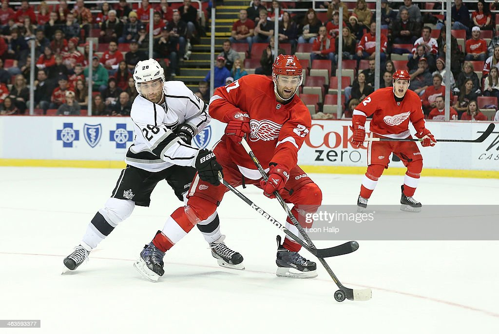 Kyle Quincey #27 of the Detroit Red Wings battles for the puck against Jarret Stoll #28 of the Los Angeles Kings during the third period of the game at Joe Louis Arena on January 18, 2014 in Detroit, Michigan. The Wings defeated the Kings 3-2 in a shootout.