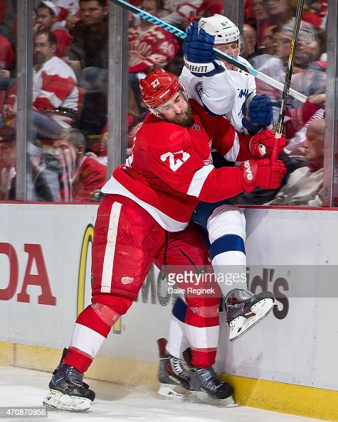 Kyle Quincey of the Detroit Red Wings body checks Andrej Sustr of the Tampa Bay Lightning into the boards in Game Three of the Eastern Conference...