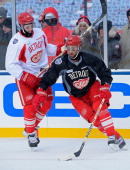 Kyle Quincey of the Detroit Red Wings controls the puck against teammate Joakim Andersson during the 2014 Bridgestone NHL Winter Classic team...