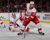 Kyle Quincey of the Detroit Red Wings defends the net in front of teammate Jimmy Howard during an NHL game on March 20 2014 at Joe Louis Arena in...