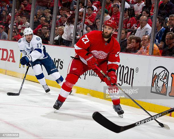 Kyle Quincey of the Detroit Red Wings handles the puck in the corner while Alex Killorn of the Tampa Bay Lightning pressures him in Game Four of the...