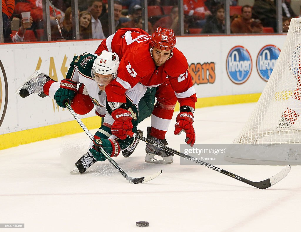 <a gi-track='captionPersonalityLinkClicked' href=/galleries/search?phrase=Kyle+Quincey&family=editorial&specificpeople=2234340 ng-click='$event.stopPropagation()'>Kyle Quincey</a> #27 of the Detroit Red Wings tries to jump over <a gi-track='captionPersonalityLinkClicked' href=/galleries/search?phrase=Mikael+Granlund&family=editorial&specificpeople=5649678 ng-click='$event.stopPropagation()'>Mikael Granlund</a> #64 of the Minnesota Wild to get to a third period puck at Joe Louis Arena on January 25, 2013 in Detroit, Michigan. Detroit won the game 5-3.