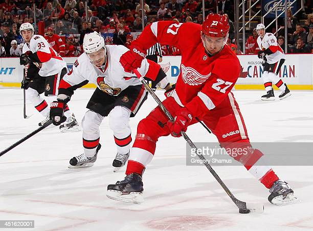 Kyle Quincey of the Detroit Red Wings tries to settle the puck in front of Milan Michalek of the Ottawa Senators during the first period at Joe Louis...