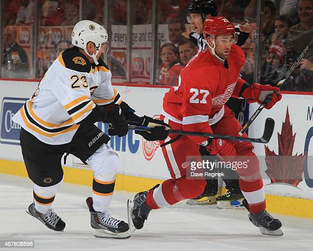 Kyle Quincey of the Detroit Red Wings tries to skate past the defending Chris Kelly of the Boston Bruins during a NHL game on October 15 2014 at Joe...