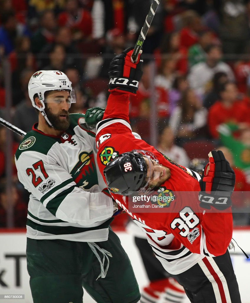 Kyle Quincey #27 of the Minnesota Wild knocks down Ryan Hartman #38 of the Chicago Blackhawks at the United Center on October 12, 2017 in Chicago, Illinois. The Wild defeated the Blackhawks 5-2.