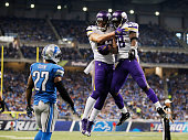 Kyle Rudolph of the Minnesota Vikings celebrates a second quarter touchdown with Adrian Peterson while playing the Detroit Lions at Ford Field on...