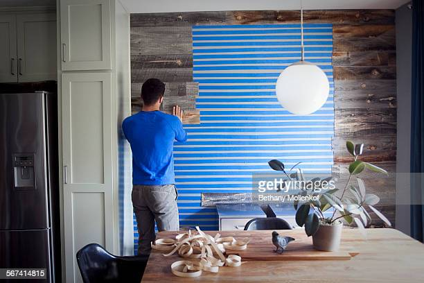 Kyle Schuneman shows how to add architecture to an apartment with a wall of reclaimed wood paneling Step 4 Application of boards to taped wall