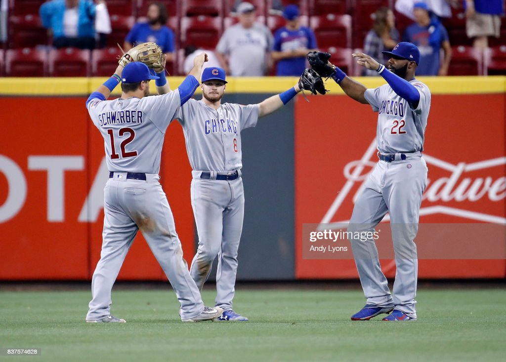 Kyle Schwarber #12, Ian Happ #8 and Jason Heyward #22 of the Chicago Cubs celebrate after the final out of the13-9 win against the Cincinnati Reds at Great American Ball Park on August 22, 2017 in Cincinnati, Ohio.
