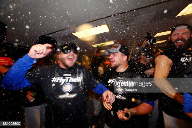 Kyle Schwarber of the Chicago Cubs celebrates with teammates in the clubhouse after winning Game 5 of the National League Division Series 98 against...
