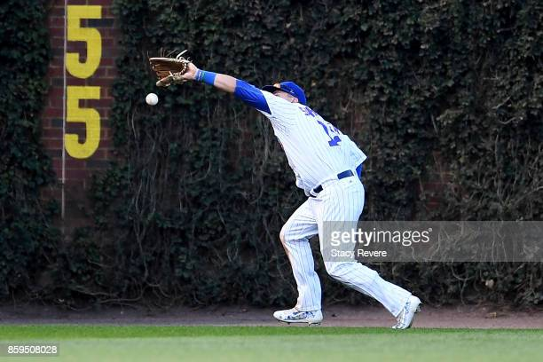 Kyle Schwarber of the Chicago Cubs commits an error in the sixth inning against the Washington Nationals during game three of the National League...