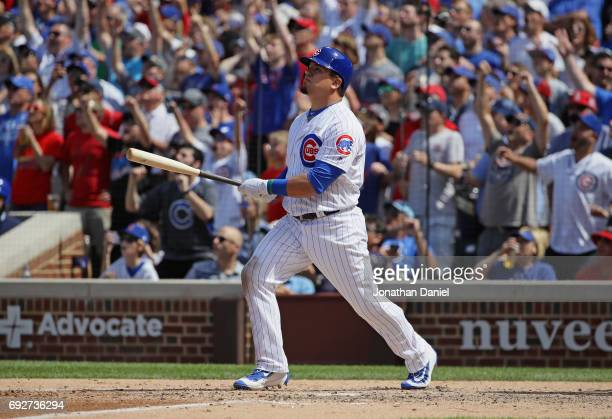 Kyle Schwarber of the Chicago Cubs follows the flight of his grand slam home run in the 7th inning against the St Louis Cardinals at Wrigley Field on...