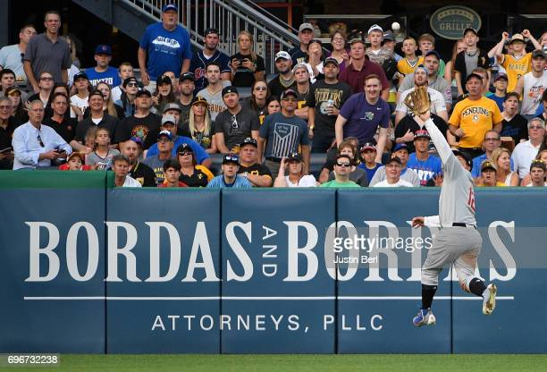 Kyle Schwarber of the Chicago Cubs makes a leaping catch on a ball off the bat of Jordy Mercer of the Pittsburgh Pirates in the third inning during...