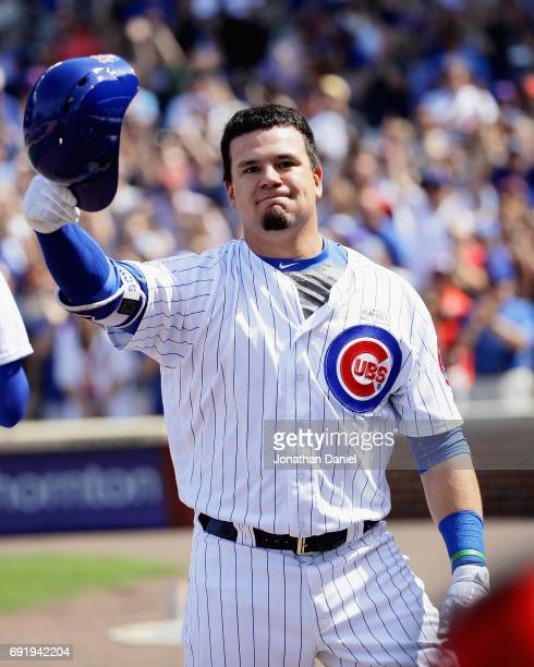 Kyle Schwarber of the Chicago Cubs tips his helmet to the crowd after hitting a grand slam home run in the 7th inning against the St Louis Cardinals...