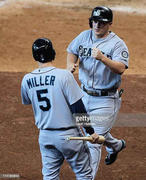 Kyle Seager and Brad Miller of the Seattle Mariners celebrate after Seager scored a run in the fifth inning against the Houston Astros at Minute Maid...