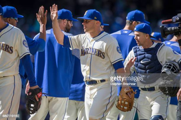 Kyle Seager of the Seattle Mariners and teammates including Tuffy Gosewisch of the Seattle Mariners celebrate beating the Texas Rangers in a game at...