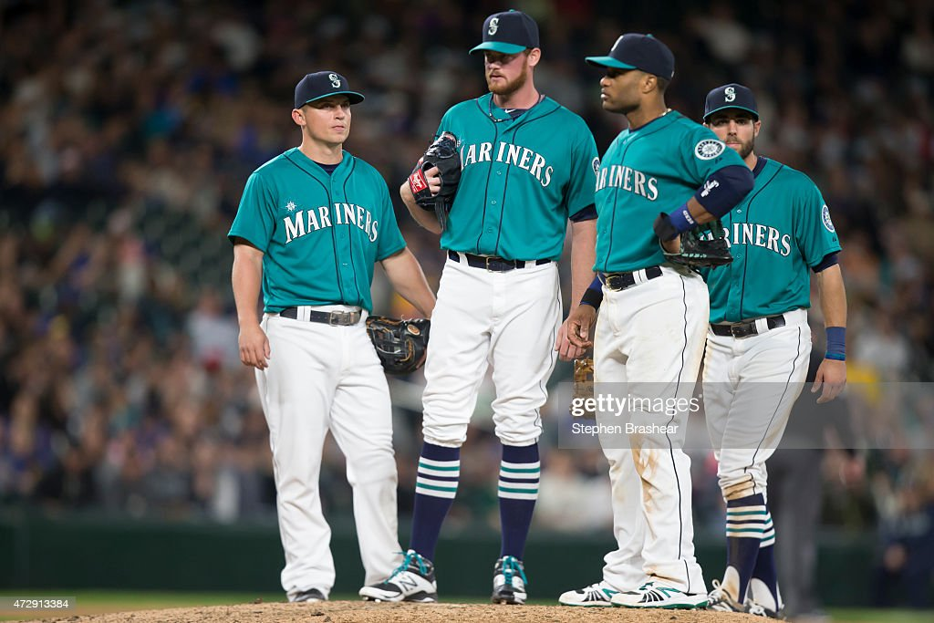 <a gi-track='captionPersonalityLinkClicked' href=/galleries/search?phrase=Kyle+Seager&family=editorial&specificpeople=7682389 ng-click='$event.stopPropagation()'>Kyle Seager</a> #15 of the Seattle Mariners, Charlie Furbush #41, <a gi-track='captionPersonalityLinkClicked' href=/galleries/search?phrase=Robinson+Cano&family=editorial&specificpeople=538362 ng-click='$event.stopPropagation()'>Robinson Cano</a> #22 and <a gi-track='captionPersonalityLinkClicked' href=/galleries/search?phrase=Chris+Taylor+-+Baseball+Player&family=editorial&specificpeople=13511734 ng-click='$event.stopPropagation()'>Chris Taylor</a> #1 meet at the pitcher's mound during a game against the Oakland Athletics at Safeco Field on May 8, 2015 in Seattle, Washington. The Mariners won the game 4-3 in eleven innings.