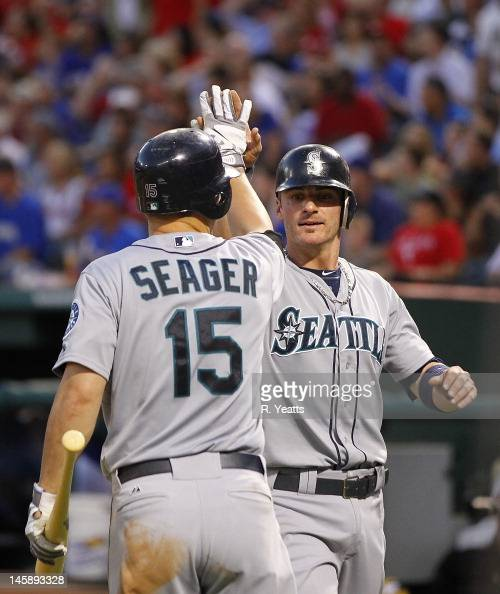 Kyle Seager of the Seattle Mariners congratulates Brendan Ryan for scoring on a sacrifice fly at Rangers Ballpark in Arlington on May 29 2012 in...