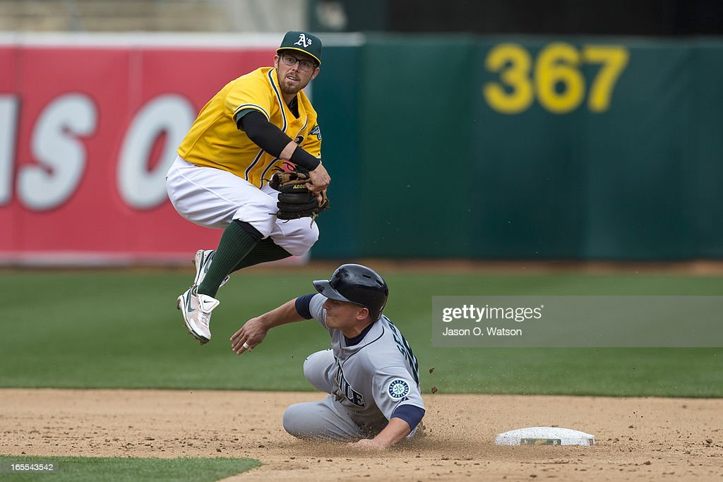 <a gi-track='captionPersonalityLinkClicked' href=/galleries/search?phrase=Kyle+Seager&family=editorial&specificpeople=7682389 ng-click='$event.stopPropagation()'>Kyle Seager</a> #15 of the Seattle Mariners disrupts a double play attempt by <a gi-track='captionPersonalityLinkClicked' href=/galleries/search?phrase=Eric+Sogard&family=editorial&specificpeople=6796459 ng-click='$event.stopPropagation()'>Eric Sogard</a> #28 of the Oakland Athletics during the sixth inning at O.co Coliseum on April 4, 2013 in Oakland, California. The Oakland Athletics defeated the Seattle Mariners 8-2.