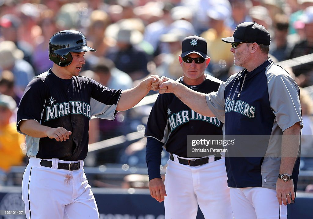 Kyle Seager #15 of the Seattle Mariners high-fives manager Eric Wedge after Seager scored a first inning run against the Colorado Rockies during the spring training game at Peoria Stadium on March 4, 2013 in Peoria, Arizona.