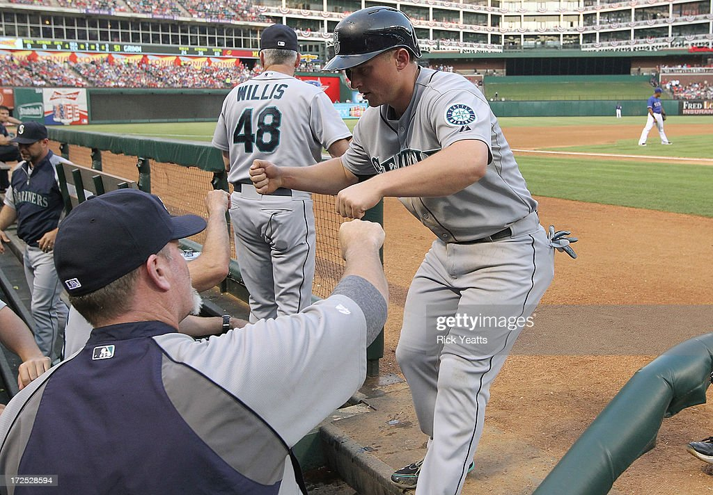 Kyle Seager #15 of the Seattle Mariners is congratulated by manager Eric Wedge #22 for scoring on a double hit by Dustin Ackley #13 against the Texas Rangers at Rangers Ballpark in Arlington on July 2, 2013 in Arlington, Texas.