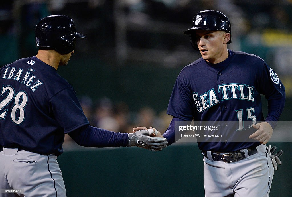 <a gi-track='captionPersonalityLinkClicked' href=/galleries/search?phrase=Kyle+Seager&family=editorial&specificpeople=7682389 ng-click='$event.stopPropagation()'>Kyle Seager</a> #15 of the Seattle Mariners is congratulated by <a gi-track='captionPersonalityLinkClicked' href=/galleries/search?phrase=Raul+Ibanez&family=editorial&specificpeople=206118 ng-click='$event.stopPropagation()'>Raul Ibanez</a> #28 after Seager scored against the Oakland Athletics in the fifth inning at O.co Coliseum on April 2, 2013 in Oakland, California.