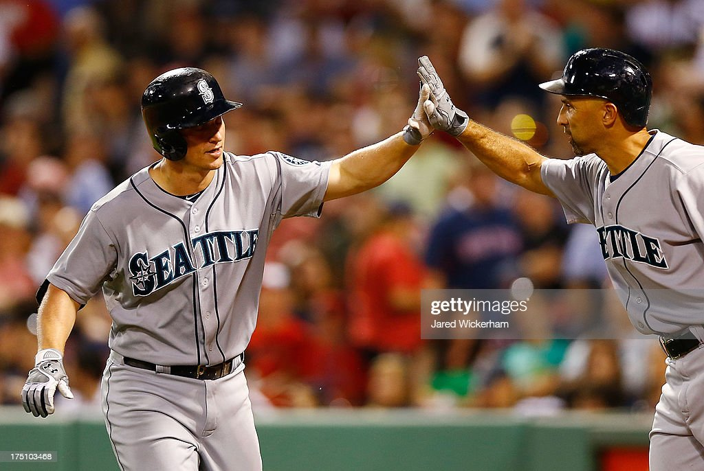 Kyle Seager #15 of the Seattle Mariners is congratulated by teammate Raul Ibanez #28 of the Seattle Mariners after hitting a solo home run in the 7th inning against the Boston Red Sox during the game on July 31, 2013 at Fenway Park in Boston, Massachusetts.