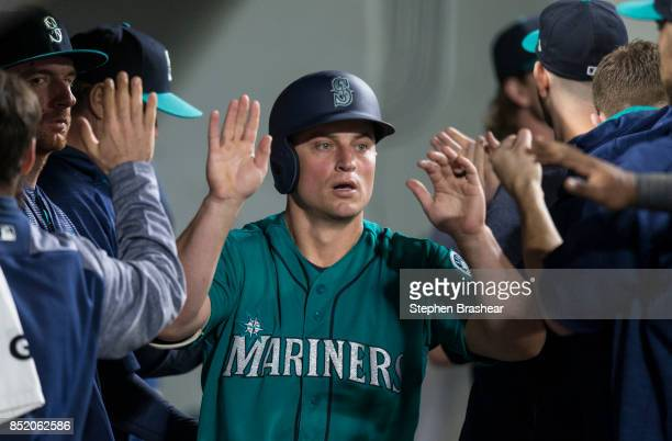 Kyle Seager of the Seattle Mariners is congratulated by teammates in the dugout after scoring a run on a hit by Yonder Alonso of the Seattle Mariners...