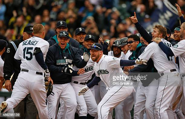 Kyle Seager of the Seattle Mariners is greeted by teammates at home plate after hitting the game winning walkoff 3run homer to defeat the Houston...