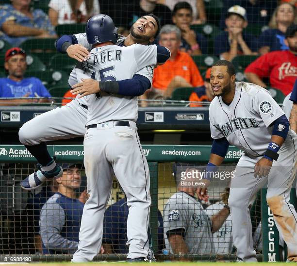 Kyle Seager of the Seattle Mariners is hugged by Nelson Cruz after Seager's home run as Robinson Cano looks on in the 10th inning against the Houston...