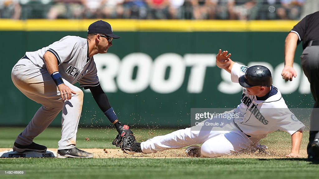 Kyle Seager #15 of the Seattle Mariners is tagged out on a steal attempt at second base by shortstop Derek Jeter #2 of the New York Yankees at Safeco Field on July 25, 2012 in Seattle, Washington. The Yankees defeated the Mariners 5-2.