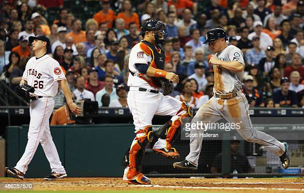 Kyle Seager of the Seattle Mariners races home in front of Hank Conger and Scott Kazmir of the Houston Astros in the fifth inning of their game at...