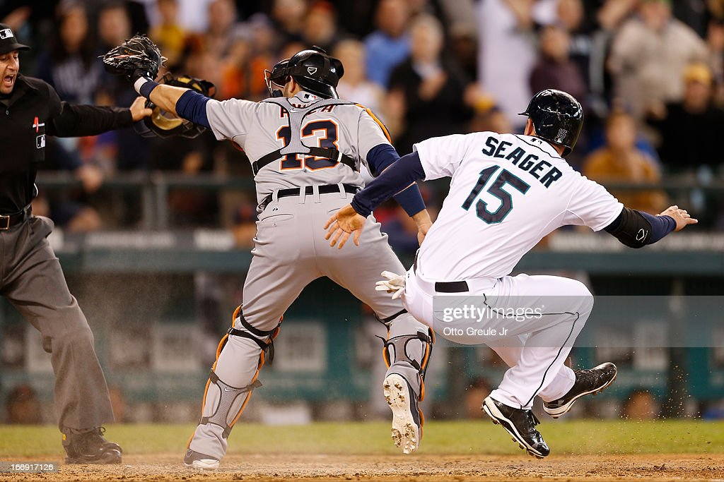 Kyle Seager #15 of the Seattle Mariners scores on an RBI single by Endy Chavez against catcher Alex Avila #13 of the Detroit Tigers as home plate umpire Jim Reynolds calls the play safe in the seventh inning at Safeco Field on April 18, 2013 in Seattle, Washington. The Mariners defeated the Tigers 2-0.