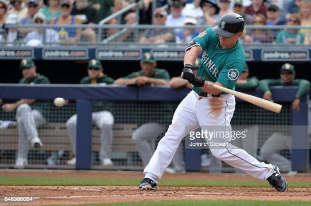 Kyle Seager of the Seattle Mariners singles in the first inning against the Oakland Athletics during the spring training game at Peoria Stadium on...
