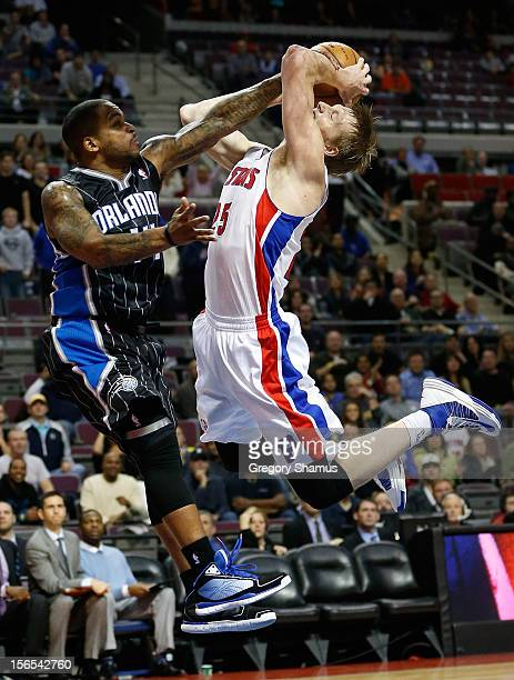 Kyle Singler of the Detroit Pistons tries to get a shot off against Jameer Nelson of the Orlando Magic at the Palace of Auburn Hills on November 16...