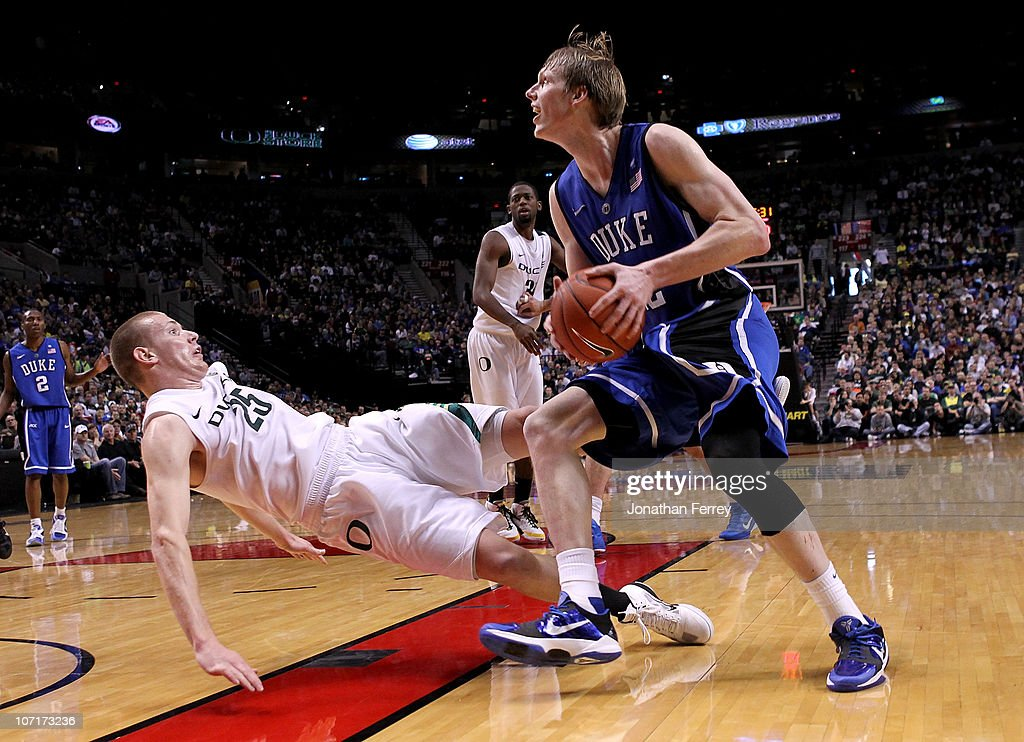 Kyle Singler of the Duke Blue Devils drives against his brother E J Singler of the Oregon Ducks on November 27 2010 at the Rose Garden in Portland...