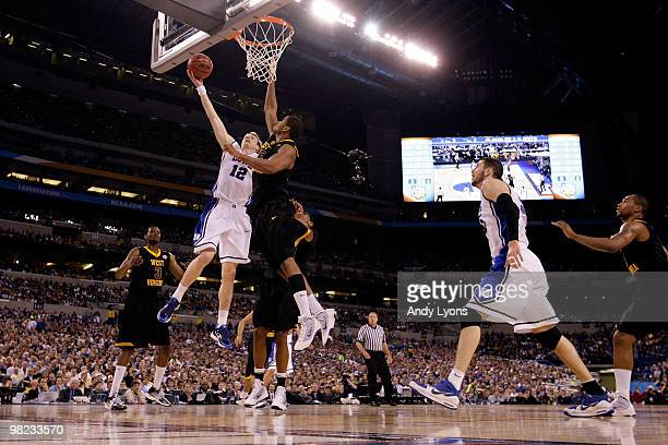 Kyle Singler of the Duke Blue Devils drives for a shot attempt in the first half against Wellington Smith of the West Virginia Mountaineers during...