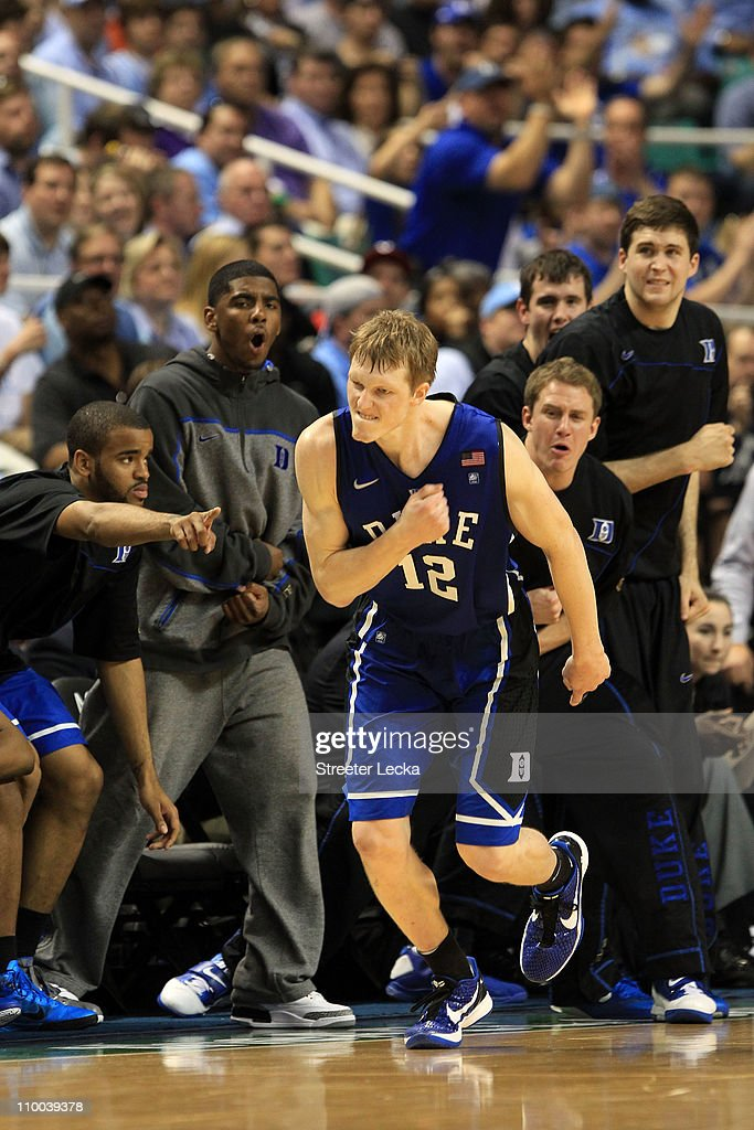 Kyle Singler #12 of the Duke Blue Devils reacts as teammate Kyrie Irving #1 and the bench cheer him on during the second half of the game against the North Carolina Tar Heels in the championship game of the 2011 ACC men's basketball tournament at the Greensboro Coliseum on March 13, 2011 in Greensboro, North Carolina.