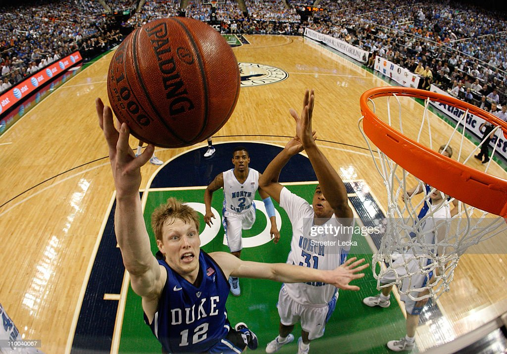 Kyle Singler of the Duke Blue Devils shoots against John Henson of the North Carolina Tar Heels in the championship game of the 2011 ACC men's...