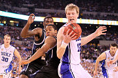 Kyle Singler of the Duke Blue Devils with the ball against Ronald Nored of the Butler Bulldogs in the first half during the 2010 NCAA Division I...
