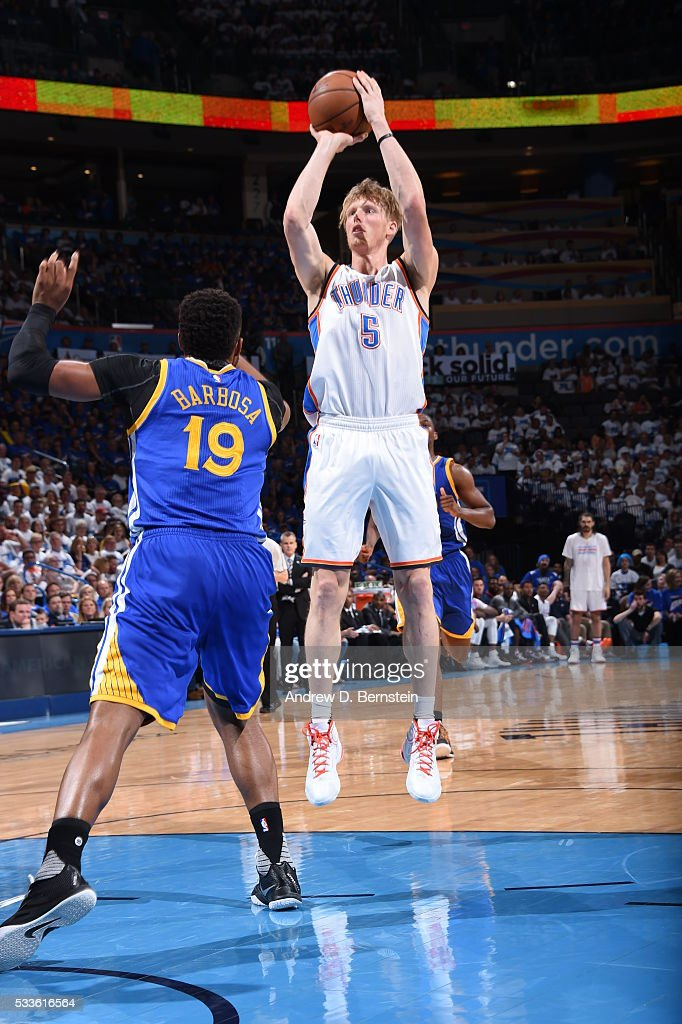 Kyle Singler of the Oklahoma City Thunder shoots against Leandro Barbosa of the Golden State Warriors in Game Three of the Western Conference Finals...