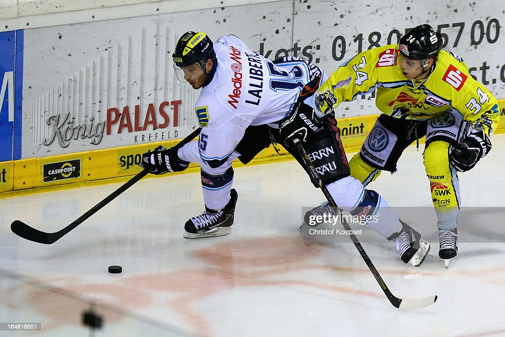 Kyle Sonnenburg of Krefeld Pinguine (R) challenges John Laliberte of ERC Ingolstadt (L) during the fifth DEL Play-Off-match between Krefeld Pinguine and ERC Ingolstadt at Koenigspalast on March 28, 2013 in Wuppertal, Germany.