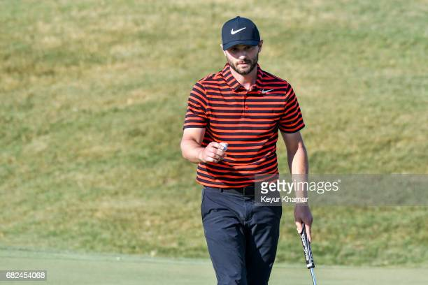 Kyle Stanley celebrates and waves his ball to fans after making a closing birdie putt on the ninth hole green during the second round of THE PLAYERS...