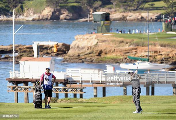 Kyle Stanley hits a shot on the fourth hole as his caddie looks on during the third round of the ATT Pebble Beach National ProAm at the Pebble Beach...
