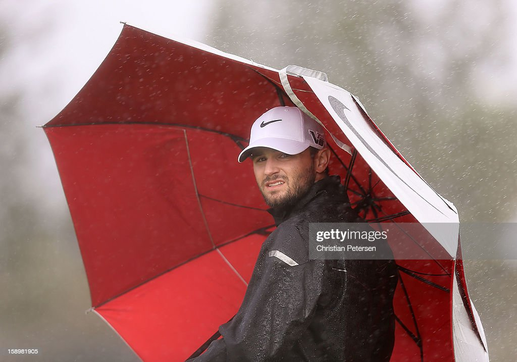 Kyle Stanley shields himself from the wind and rain under an umbrella on the second hole green during the first round of the Hyundai Tournament of Champions at the Plantation Course on January 4, 2013 in Kapalua, Hawaii.