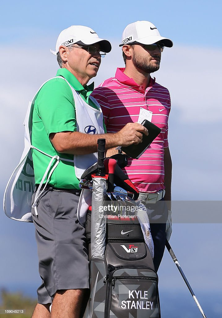 Kyle Stanley (R) stands with his caddie and bag before taking a tee shot on the 10th hole during the replay of the first round of the Hyundai Tournament of Champions at the Plantation Course on January 6, 2013 in Kapalua, Hawaii.